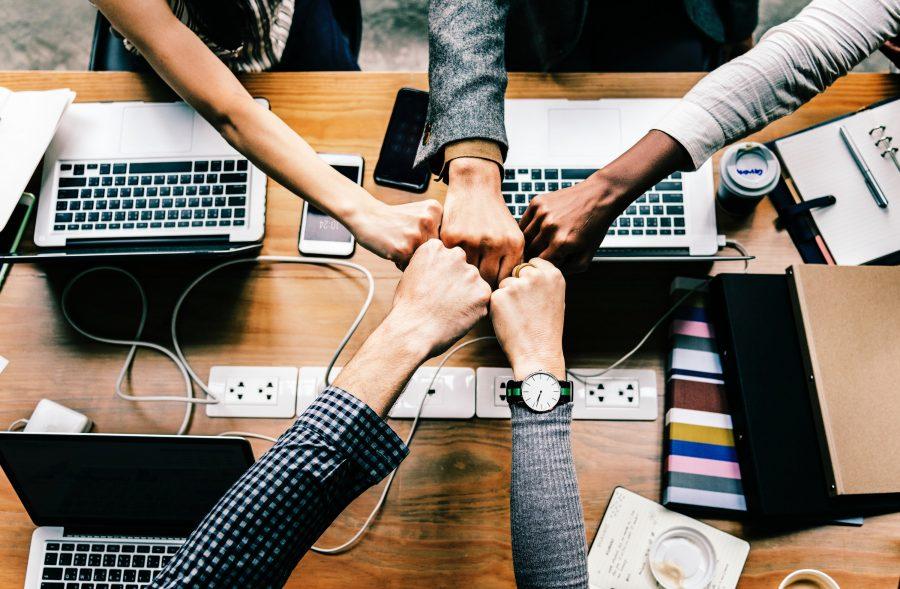 Fünf Leute die als Team arbeiten und zusammen einschlagen