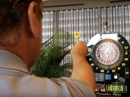 Mann mit Dartpfeil in der Hand bei Darts Firmenfeier