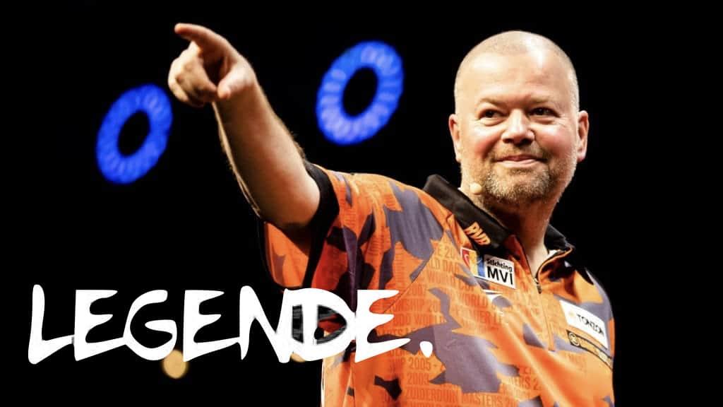 Raymond van Berneveid lächelt und zeigt mit seinem Finger auf etwas, schwarzer Hintergrund mit zwei blaue Ringe