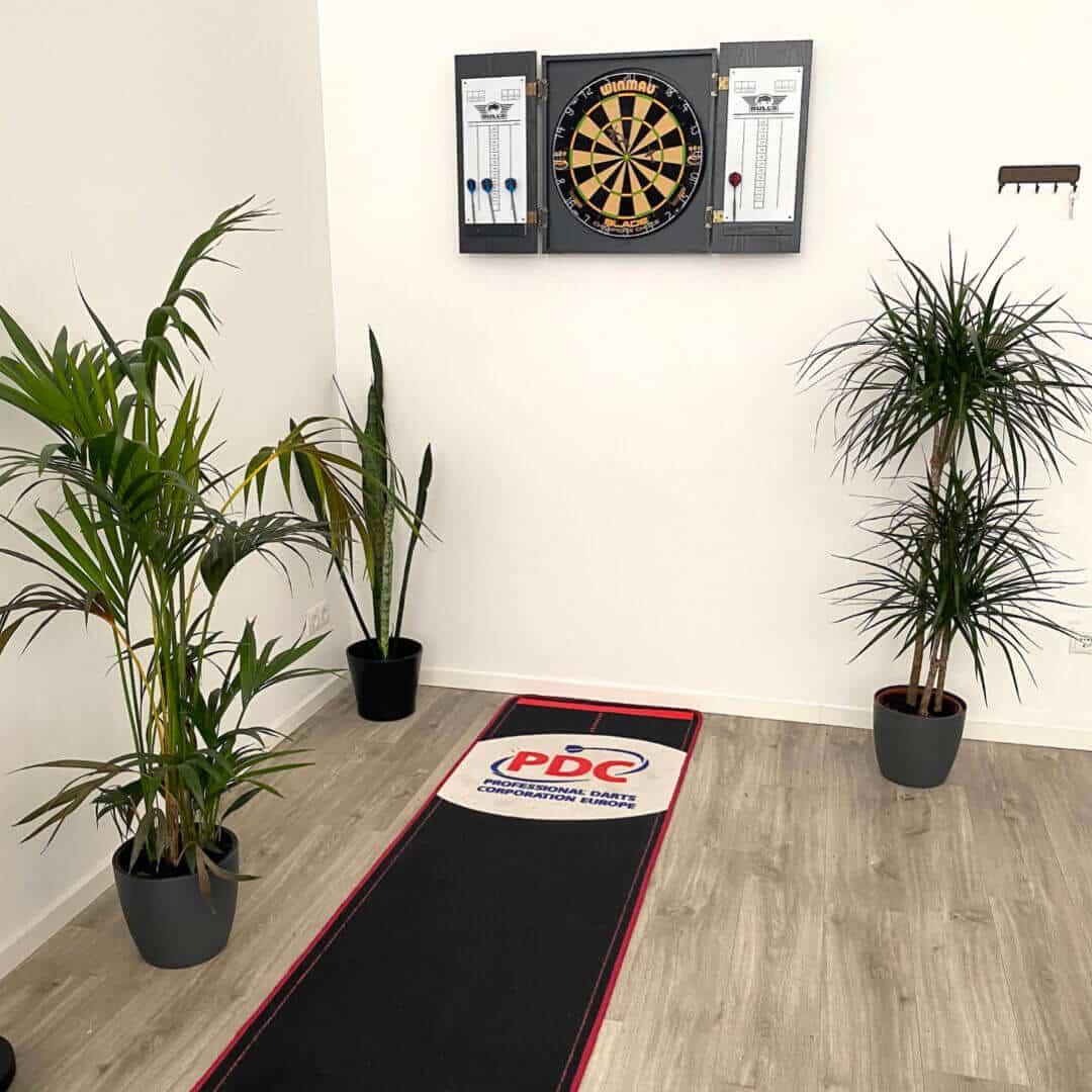 Dartraum mit schwarzem Darts Teppich, grünen Pflanzen und Dartscheibe mit Dart Kabinett