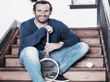 Ein Mann sitz auf einer Treppe mit einen Tennisschläger. Daneben befindet sich ein Tennisball