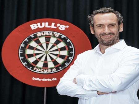 Ein Mann steht vor einer Dartscheibe und trägt ein weißes Hemd