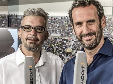 Zwei Lächelnde Männer, die graue Mikrofone halten