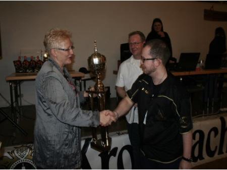Eine Person gibt jemandem ein Pokal und gratuliert ihm