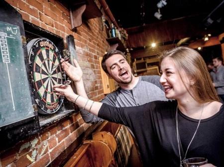 Eine Frau und ein Mann spielen Darts im Darts Bar