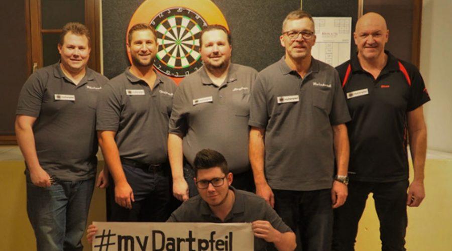 Dart Mannschaft aus 6 Dartspieler - 5 Stehend und 1 Kniend - mit myDartpfeil Banner